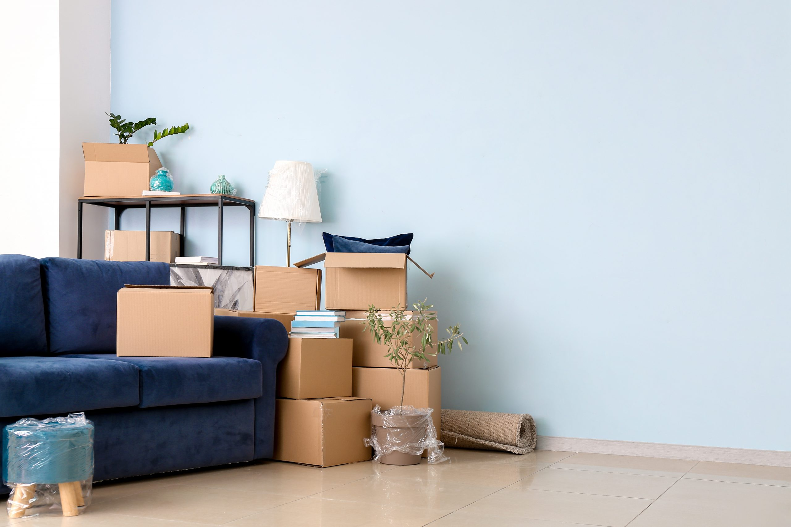 Cardboard boxes with belongings and sofa in new flat on moving day